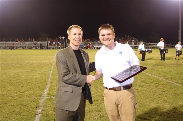 Pleat & Perry accepts plaque from Destin Middle School Band Director